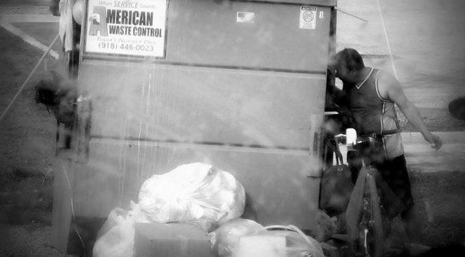 homeless-man-on-bicycle-digging-through-trash